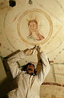 Roman fresco  Restorer injecting a resin to strengthen a fresco on the ceiling of a Roman burial site  The fresco is of the Roman goddess of the Moon,...