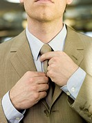 Young businessman adjusting tie, mid section, close-up