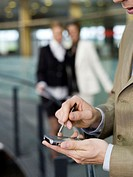 Young businessman using mobile phone, women talking in background (thumbnail)