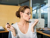Woman in office, applying nail polish, blowing, close-up