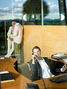 Businesswoman in office using phone, colleagues talking behind