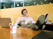 Young man in office having lunch break