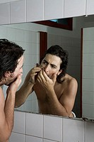 Man wrapped in towel admiring himself in a mirror