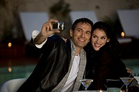 Couple taking pictures of themselves enjoying candlelit drinks by swimming pool