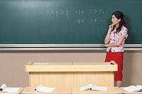 Teacher contemplating words on the blackboard