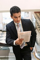 Businessman reading newspaper while on escalator