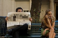 Businessman peeking over his newspaper outdoors at woman beside him