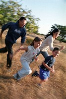 Family in park running in field