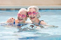 Two senior women laughing in swimming pool
