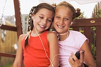 Pre-teen girls listening to mp3 player