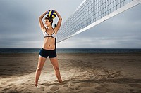 Mid-adult woman posing with volleyball on beach