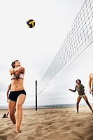 Small group of people playing volleyball on beach