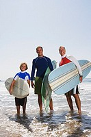 Three generations standing on shore with surfboards