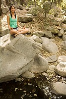 Woman seated on rock in meditative pose