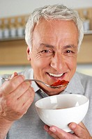 Gray-haired man holding a spoon and a bowl, close-up
