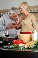 Blonde woman lets a gray-haired man taste something she has cooked, selective focus