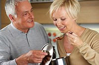 Blonde woman tasting something a grey-haired man has cooked