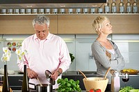 Blond woman turned away from a man who is cooking