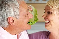 Blonde woman feeding a grey-haired man with a lettuce leaf, close-up
