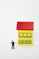 Businessman figurine standing in front of a house