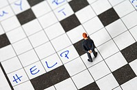 Businessman figurine on a crossword puzzle