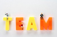 Male and female figurines sitting on letters of the word team