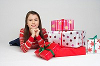 Girl lying on front next to Christmas presents (thumbnail)