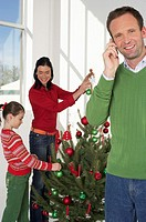 Family in Christmassy room, father phoning with a mobile phone, mother and daughter decorating the Christmas tree