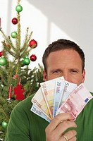 Man holding banknotes, Christmas tree in background