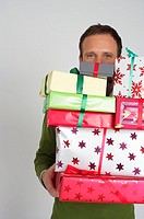 Man carrying a stack of Christmas presents