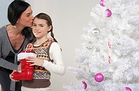 Mother kissing daughter's forehead next to a white Christmas tree