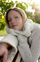 Young woman in a cardigan on a wooden bench, close-up, selective focus