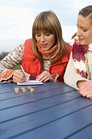 Two young women gambling with dice