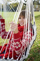 Young woman in warm clothing sitting on a hammock, close-up