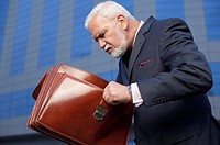 Mature businessman looking into a briefcase