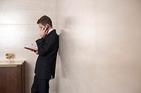 Businessman with diary, phoning with mobile phone