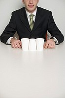 Businessman at desktop, in foreground three cups