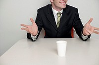 A white cup in front of a businessman