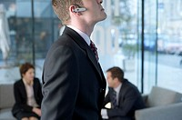 A businessman with a headset, businesspeople in the background