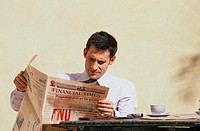 Businessman reading newspaper during a coffee break (thumbnail)