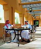 Arab men enjoying sheesha and a game of backgammon