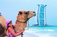 Western tourist touching a camel on the beach in Dubai, UAE