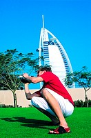 Western tourist taking pictures in front of Burj Al Arab hotel in Dubai, UAE