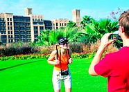 Western tourists photographing in front of Mina Al Salam hotel in dubai, UAE