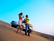 Western couple in the UAE desert with a 4x4 car