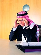 Saudi Arabian businessman holding his head