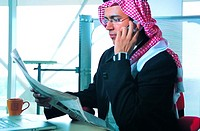 Saudi Arabian businessman reading newspaper in office