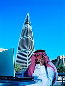 Saudi Businessman working on Laptop near Faisaliah Tower in Riyadh, Saudi Arabia