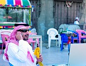 Saudi businessman using mobile phone and laptop in Old Town of Jeddah, Saudi Arabia