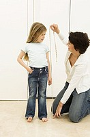 Young woman measuring the height of her daughter with a tape measure